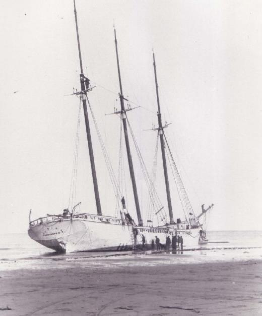 The three-masted schooner Ulrica lies on the beach as sailors climb out.